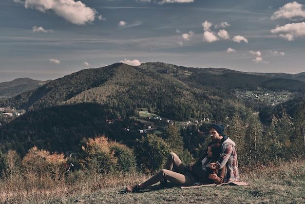 Gewoon verliefd. mooi jong koppel omarmen en wegkijken terwijl ze op het gras liggen voor het perfecte uitzicht op de bergketen