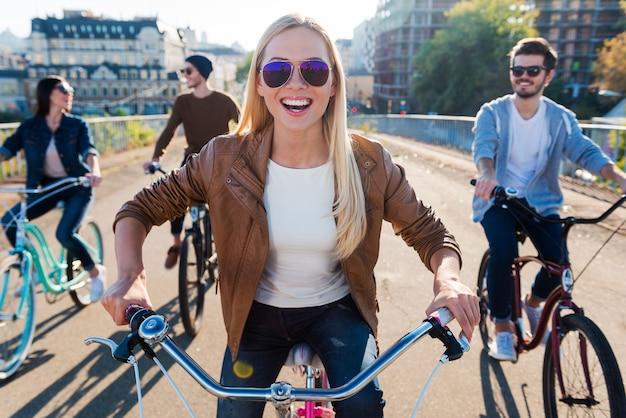 Gewoon vrienden en vooruit. mooie jonge glimlachende vrouw fietst en kijkt naar de camera terwijl haar vrienden op de achtergrond rijden