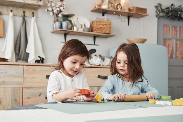 Gewoon vrije tijd hebben. twee kinderen spelen met geel en oranje speelgoed in de witte keuken.