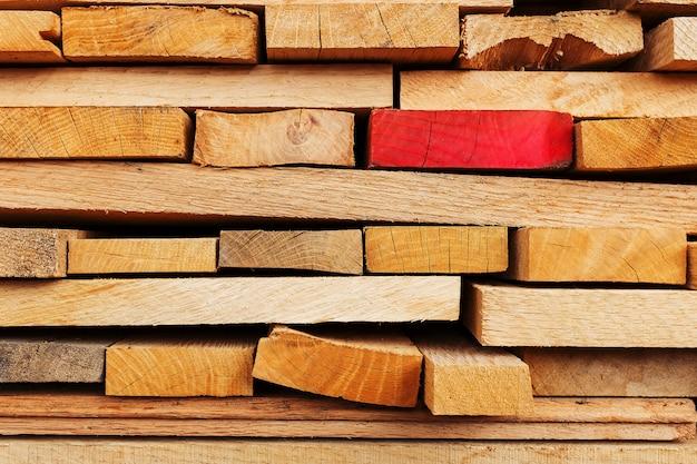 Gezaagde en gevouwen planken met de nadruk op één rood bord, constructieplanken, timmerhoutachtergrond.