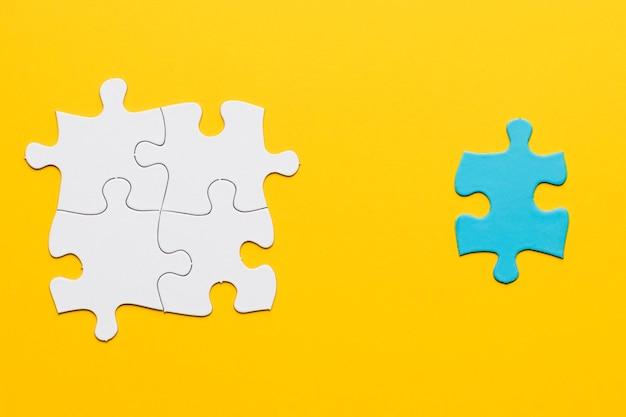 Gezamenlijke witte puzzel met een blauw stuk op geel oppervlak