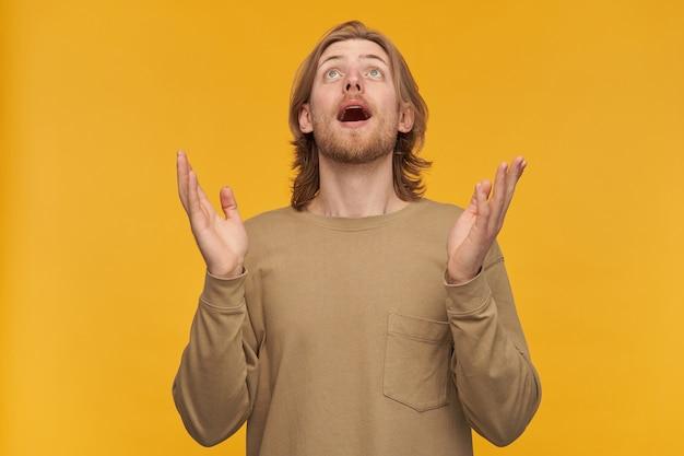 Gezegende jongeman, positieve man met blond haar, baard en snor. beige trui dragen. hij heft zijn handpalmen op en kijkt bewonderend omhoog naar de kopie ruimte, geïsoleerd over een gele muur