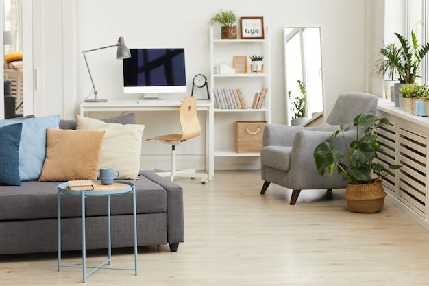 Gezellig appartement interieur in grijze en witte kleuren en focus op moderne bank met decorelementen
