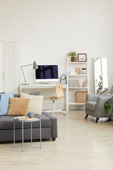 Gezellig appartementinterieur in minimaal scandinavisch design en focus op grijze bank met decorelementen