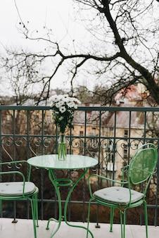 Gezellig balkon met groene tafel en stoelen