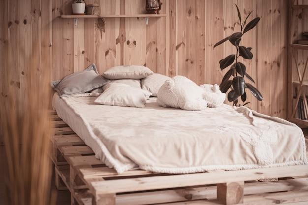 Gezellig bed met kussens en bear speelgoed in houten interieur.