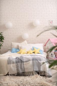 Gezellig bed met licht linnengoed, gebreide dekens en kussens