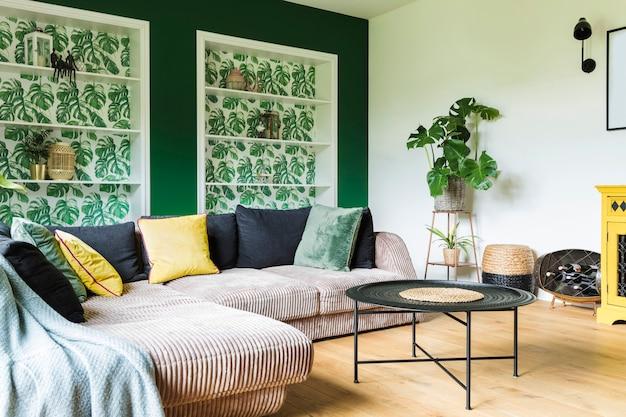Gezellig en stijlvol woonkamerinterieur met grote hoekbank, meubels, kussens en andere accessoires en decoraties. groene muren, mediterrane stijl.