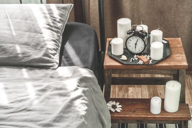 Gezellig grijs slaapkamerbinnenland met comfortabel bed dichtbij houten nachtlijst met kaars
