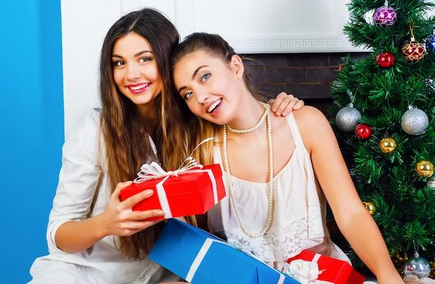 Gezellig helder wit vakantieportret van twee beste vrienden, mooie zussen, zittend bij de open haard en een versierde kerstboom en met cadeautjes van hun familie. positieve emoties en stemming.