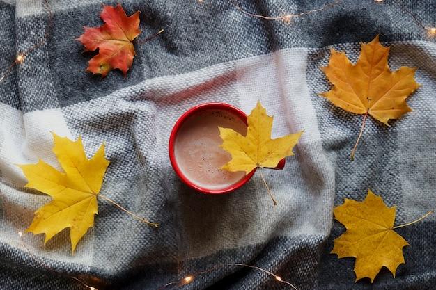 Gezellig herfsthuis plat gelegd. een kopje cacao op een plaid deken met herfst esdoorn bladeren.