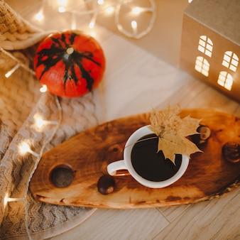 Gezellig herfststilleven met pompoen en een kopje koffie op een gebreide beige plaid met bokehlichten