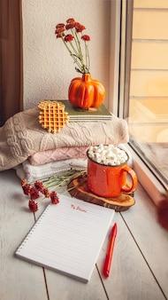 Gezellig herfststilleven op de vensterbank met notitieblok voor notities: warme wollen truien, pompoenen, esdoornbladeren en een kopje cacao met marshmallows en wafels.