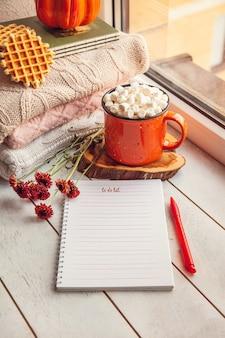 Gezellig herfststilleven op de vensterbank: warme wollen truien, pompoenen, esdoornbladeren en een kopje cacao met marshmallows en wafels.