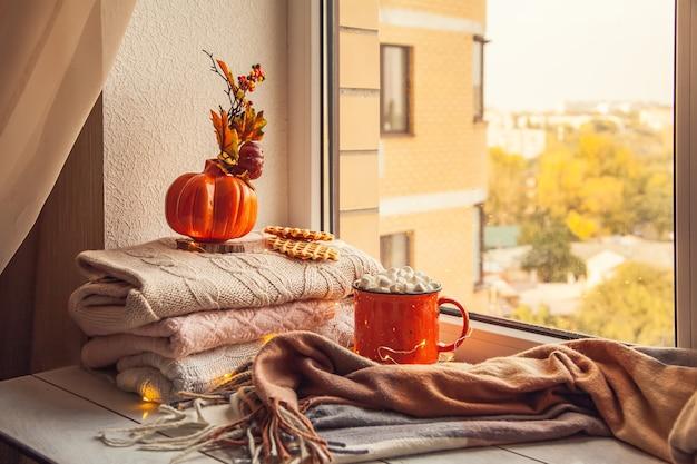 Gezellig herfststilleven op de vensterbank: warme wollen truien, sjaal, pompoenen, esdoornbladeren en een kopje cacao met marshmallows en wafels.