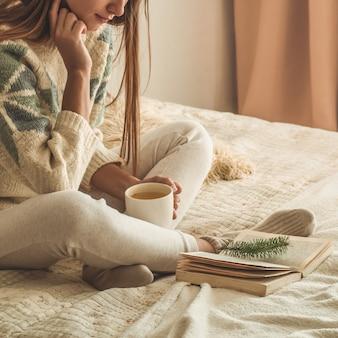 Gezellig huis. de mooie vrouw leest een boek op het bed. goedemorgen met thee en boek. vrij het jonge vrouw ontspannen. het concept van lezen