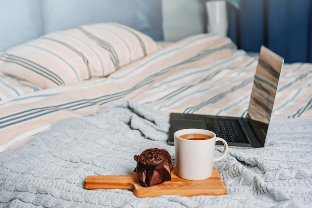 Gezellig huis, interieur en winter, concept slaapkamer met laptop, koffiekopje en muffin