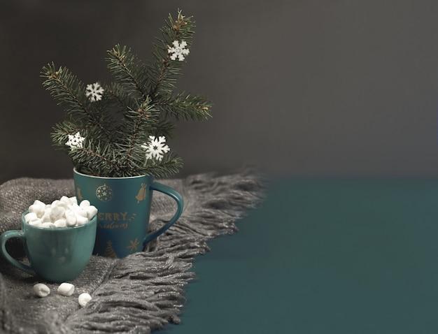 Gezellig huis knuffelen kerstmis of nieuwjaar achtergrond met kerstmok met dennentakken, sneeuwvlokken, kopje koffie of cacao met marshmallows op grijze gebreide plaid op donker. selectieve aandacht. kopieer ruimte.