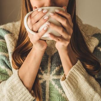 Gezellig huis. vrouw met kop warme drank bij het raam. kijkend naar het raam en drink thee. goedemorgen met thee. vrij het jonge vrouw ontspannen. gelukkig concept.