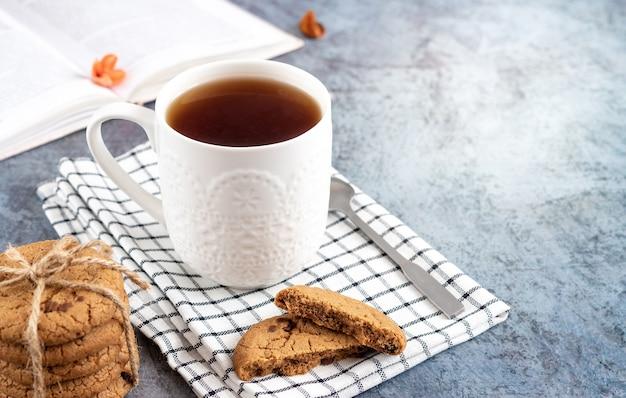 Gezellig huisconcept - open boek, kopje thee en koekjes met stukjes chocolade op een geruit servet
