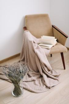 Gezellig huisdecor. fauteuil met een deken en een boek, een vaas met een boeket lavendel. modern huis interieur.