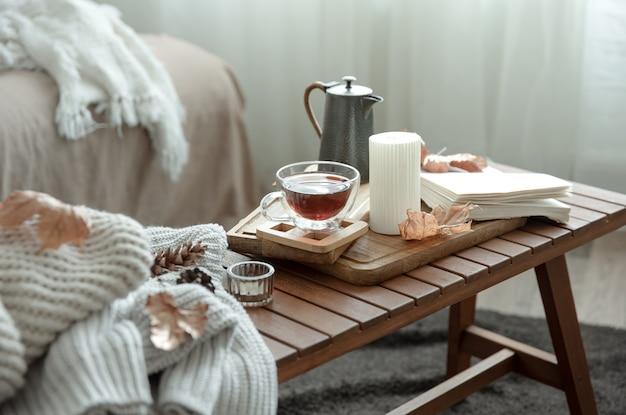Gezellig huisstilleven met een kopje thee en details van het herfsthuisdecor.
