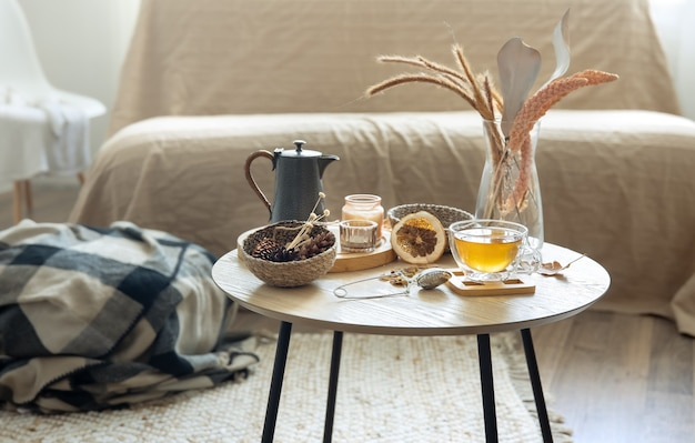 Gezellig huisstilleven met een kopje thee, pompoenen, kaarsen en details van het herfstdecor op een tafel op een onscherpe achtergrond.