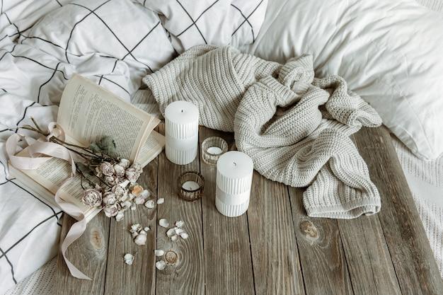 Gezellig huisstilleven met kaarsen, gebreid element, boek en bloemen.