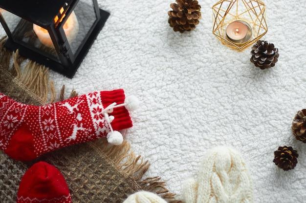 Gezellig huisstilleven: wollen handschoenen, rode wollen sokken, kegels, kaarsen met een warme wollen deken en een trui. kerstvakantie