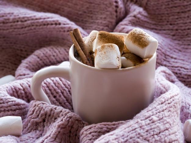 Gezellig, humeur, leefbaar, stillevenconcept. mok van aromatische cacaokoffie met marshmallows, trui en kaneel op roze gebreide truien