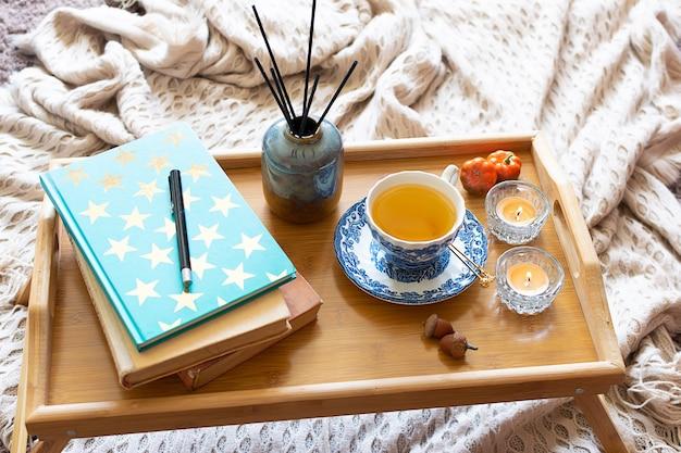 Gezellig interieur met kopje kruidenthee, aromatische kaarsen, warme deken en boeken.