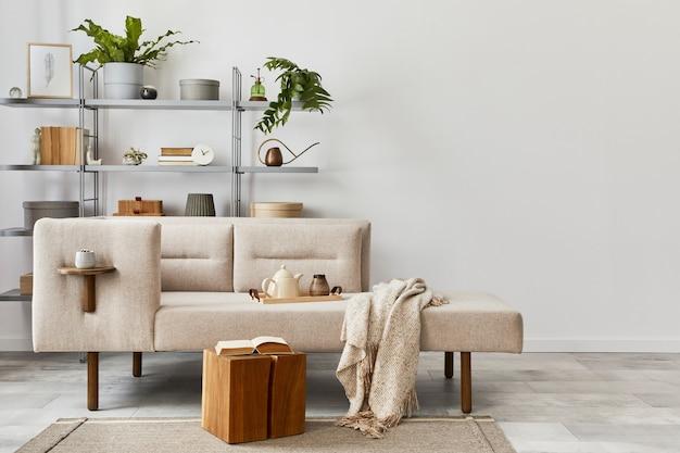 Gezellig interieur met stijlvolle bank, grijze salontafel, boekenkast, planten, tapijt, decoratie, kopieerruimte en elegante persoonlijke accessoires. neutrale woonkamer in klassiek huis..