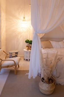 Gezellig interieur van een licht appartement in balinese stijl met witte muren en bamboe meubels. slaapkamer met nachtverlichting, bed met balanchin en grote ramen