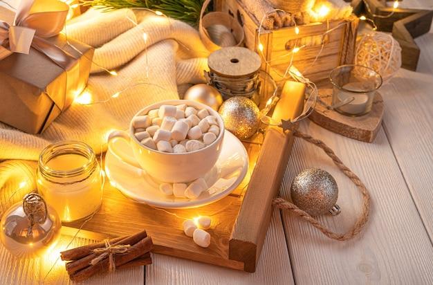 Gezellig, kerstachtergrond met koffie in het licht van een brandende slinger. het concept van kerstmis en nieuwjaar.