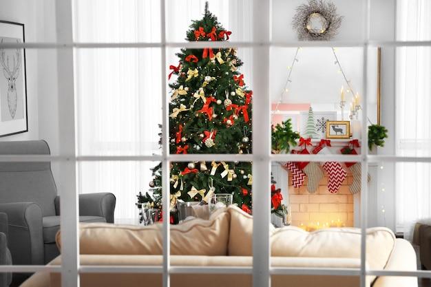 Gezellig kerstinterieur van woonkamer met prachtige dennenboom, uitzicht door raam