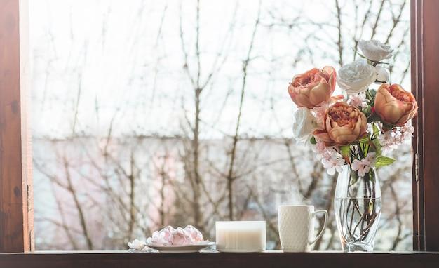 Gezellig lentestilleven: kopje hete thee met lenteboeket bloemen op vintage vensterbank met een roze marshmallow. voorjaar. appartement.