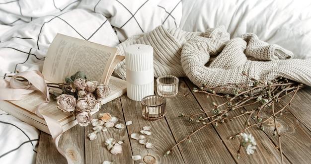 Gezellig lentestilleven met kaarsen, gebreid element, boek en bloemen.