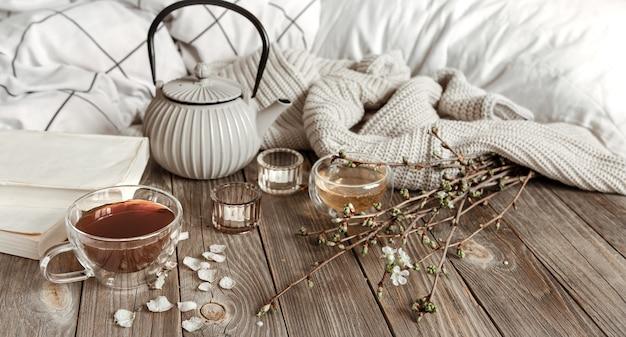 Gezellig lentestilleven met kaarsen, thee, waterkoker op een houten oppervlak in een rustieke stijl.