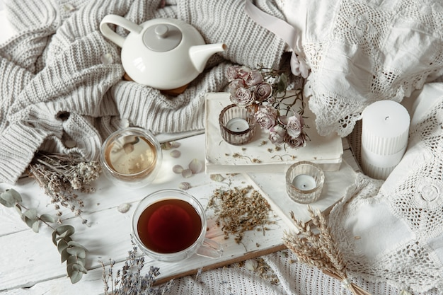Gezellig licht stilleven met kaarsen, kopjes thee, theepot en bloemen als decor.