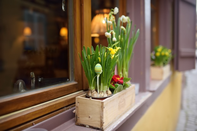 Gezellig raam van een houten huis versierd met bloemen en houten ornamenten voor pasen.