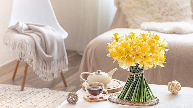 Gezellig stilleven met lentebloemen in lichte woonkamer interieur. het concept van decor en comfort.
