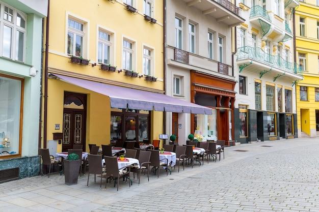 Gezellig terras aan de geplaveide straat, karlovy vary, tsjechië, europa. oude europese stad, beroemde plaats voor reizen en toerisme
