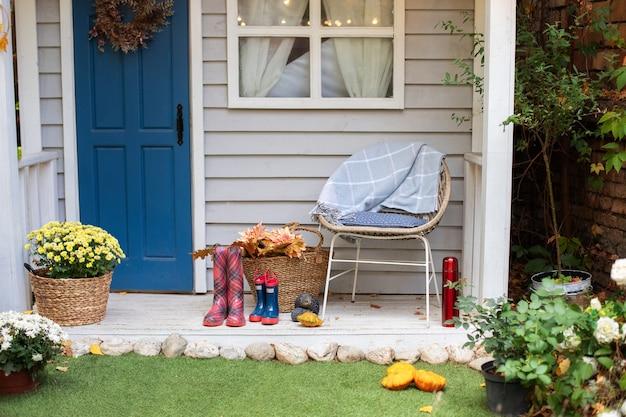 Gezellig terras met stoel, plaid, rubberen laarzen, manden met chrysanten. decoraties op de patio om te ontspannen. stijlvol decor op de veranda van het huis.