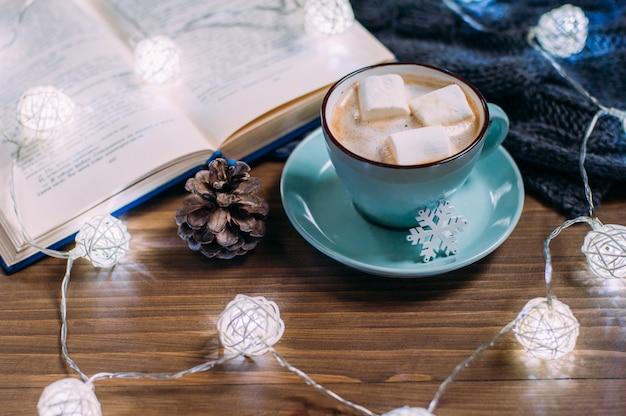 Gezellig winterhuis. kopje cacao met marshmallows, warme gebreide trui, open boek, kerstslinger op een witte houten tafel. sfeer van een aangename avond om te lezen.