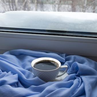 Gezellig winterstilleven: een kop warme koffie, een blauwe sjaal op de vensterbank tegen de achtergrond van een besneeuwd landschap