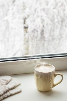Gezellig winterstilleven kopje hete koffie en warme wanten op vensterbank tegen de met sneeuw bedekte bomen buiten het raam