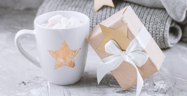 Gezellig winterweekendstilleven met schattige keramische beker, geschenkdoos en gebreide truien op grijs