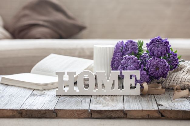 Gezellige achtergrond met decoratief woord huis, chrysantenboeket, boek en kaars.