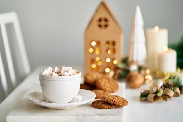 Gezellige avond winterscène kerstvakantie achtergrond met dennentak kopje warme chocolademelk