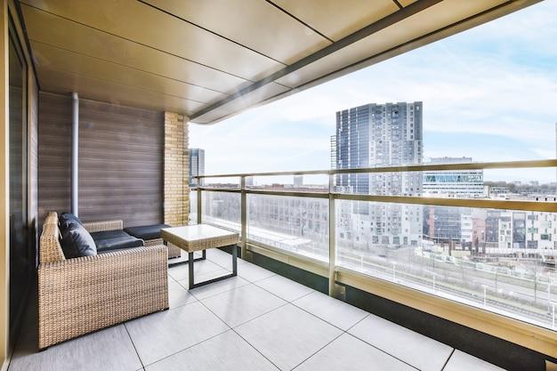 Gezellige bank en houten tafel geplaatst op balkon van flatgebouw met stadsgezicht